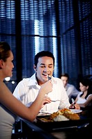 Woman feeding her boyfriend while eating at a restaurant