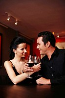 Couple locking arms,holding glass of wine