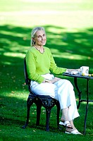 Woman enjoying a cup of coffee in the garden