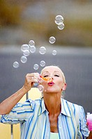Woman blowing soap bubbles (thumbnail)