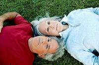 Old couple lying on the grass