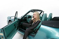 Woman, blond, Porsche, sitting, cell phone,  telephones, driver door, open,   Series, 20-30 years, businesswoman, elegantly, car turquoise Cabrio, spo...