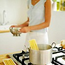 Woman cooking spaghetti at home