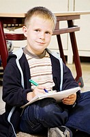 Boy looking at the camera while holding a pen and a book