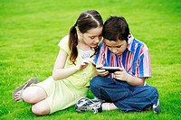 Children looking at a handheld game device