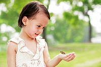 Girl looking at a frog in her hand
