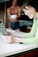 Woman with glasses reading newspaper