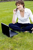 Woman talking on the mobile phone while using laptop