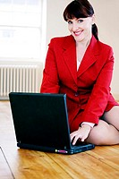 Businesswoman smiling at the camera while using laptop