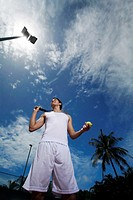 Man holding a tennis racquet and tennis ball