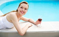 Woman with a glass of red wine relaxing on the pool side