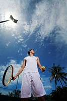 Man holding a tennis racquet and a tennis ball