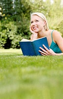 Woman daydreaming while holding a book