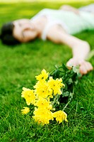 Woman lying on the grass holding flowers