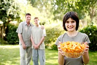 Teenage girl holding a bowl of potato chips with her father and brother standing in the background