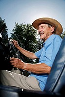 Senior man with hat traveling in a car