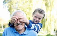 Boy covering his grandfather´s eyes
