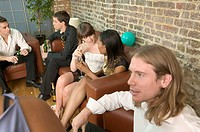 Group of young people sitting together at party (thumbnail)