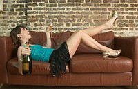 Laughing young woman lying on couch holding bottle and glass of champagne (thumbnail)