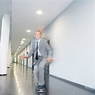 Businessman skateboarding in office building corridor (thumbnail)