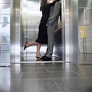 Businesswoman and man making out in elevator (thumbnail)