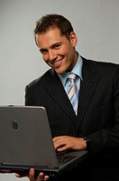Portrait of a smiling businessman with laptop (thumbnail)