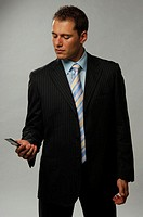Earnest businessman looking at his mobile phone