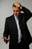 Businessman tearing his hair while looking at his mobile phone