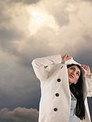 Woman protecting herself with coat from rain (thumbnail)