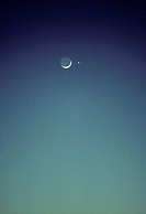 Blue twilight sky with eclipsed crescent moon