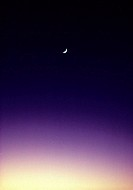 Darkening sunset sky with crescent moon