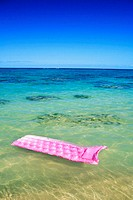 Pink inflated raft on clear ocean water