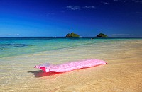 Hawaii, Oahu, Lanikai, Pink inflated raft on clear ocean water, Mokulua's in background