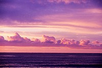 Cloudy pink sky over ocean at sunset