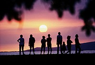 Silhouette of a group of people standing on beach watching a gorgeous sunset