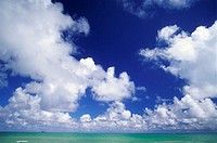 Puffy white clouds in blue sky over turquoise ocean
