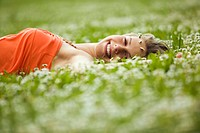 Teenage girl lying in meadow, smiling