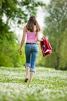 Young woman walking in meadow, rear view