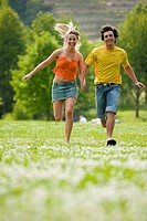 Young couple running in meadow with hand in hand