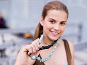 Teenage girl (16-17) holding necklace, close-up