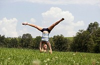 Teenage girl (13-15) making handstand in meadow