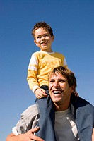 Boy (4-7) sitting on father´s shoulders, smiling, close-up