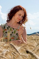Young woman standing in cornfield, looking at cornstalk