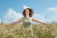 Young woman standing in cornfield, arms out, smiling