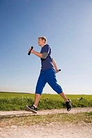 Young man jogging, carrying dumbbells