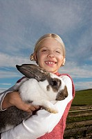 Girl holding rabbit in arms