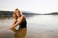 Woman sitting in lake, portrait