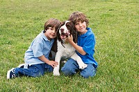 Two young boys pose with a dog on a grass lawn.