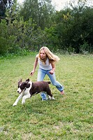 Barefoot blonde teen girl in blue jeans and white tank top running with pet dog on a grass lawn.