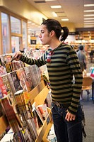 Teen boy looks through magazine rack at a bookstore